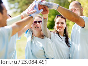 group of happy volunteers making high five in park. Стоковое фото, фотограф Syda Productions / Фотобанк Лори
