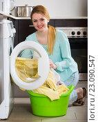Купить «Happy girl washing bed linen and towels», фото № 23090547, снято 18 октября 2018 г. (c) Яков Филимонов / Фотобанк Лори