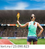 Composite image of rear view of sporty woman holding olympic torch. Стоковое фото, агентство Wavebreak Media / Фотобанк Лори