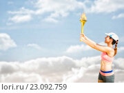 Composite image of sporty woman holding olympic torch. Стоковое фото, агентство Wavebreak Media / Фотобанк Лори