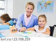 Teacher helping schoolgirl with her homework in classroom. Стоковое фото, агентство Wavebreak Media / Фотобанк Лори