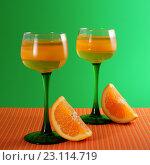 Купить «Апельсиновый десерт(желе) в высоких бокалах и дольки апельсина. Зеленый фон.», фото № 23114719, снято 15 июня 2016 г. (c) ирина реброва / Фотобанк Лори