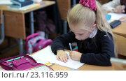 Ученица в школьной форме сидит за партой и пишет в тетради левой рукой (2016 год). Редакционное видео, видеограф Кекяляйнен Андрей / Фотобанк Лори