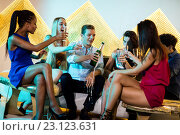Male friend popping a champagne bottle while friends watching him. Стоковое фото, агентство Wavebreak Media / Фотобанк Лори