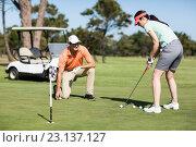 Купить «Woman playing golf while standing by man», фото № 23137127, снято 14 апреля 2016 г. (c) Wavebreak Media / Фотобанк Лори