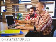 Купить «Creative male colleagues smiling while discussing over laptop», фото № 23139335, снято 10 апреля 2016 г. (c) Wavebreak Media / Фотобанк Лори