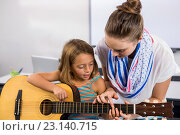Купить «Close-up of teacher assisting girl to play guitar in classroom», фото № 23140715, снято 9 апреля 2016 г. (c) Wavebreak Media / Фотобанк Лори