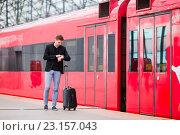 Купить «Молодой мужчина стоит на перроне вокзала и смотрит на часы», фото № 23157043, снято 9 июня 2016 г. (c) Дмитрий Травников / Фотобанк Лори