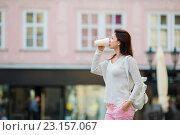 Молодая женщина пьет кофе из одноразового стаканчика на фоне города. Стоковое фото, фотограф Дмитрий Травников / Фотобанк Лори