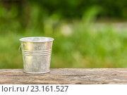 Купить «Пустое ведро на фоне зеленых листьев», фото № 23161527, снято 19 июня 2016 г. (c) Йомка / Фотобанк Лори