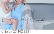 Купить «Mother using laptop while holding her baby in her hands», видеоролик № 23162883, снято 10 апреля 2020 г. (c) Wavebreak Media / Фотобанк Лори