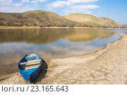 Купить «Лодка на берегу реки на фоне гористого берега», фото № 23165643, снято 5 апреля 2016 г. (c) Борис Панасюк / Фотобанк Лори