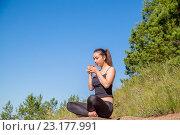 Девушка в позе лотоса с кружкой в руках сидит на камне. Стоковое фото, фотограф Виктор Хван / Фотобанк Лори