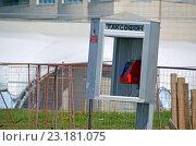 Купить «Старый покосившийся таксофон на фоне решетки - заграждения строительной площадки», эксклюзивное фото № 23181075, снято 29 июня 2016 г. (c) Александр Замараев / Фотобанк Лори