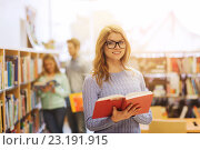Купить «happy student girl or woman with book in library», фото № 23191915, снято 6 марта 2015 г. (c) Syda Productions / Фотобанк Лори