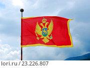 Флаг Черногории на фоне неба с облаками. Стоковое фото, фотограф Алексей C. / Фотобанк Лори