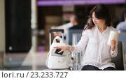 Купить «Девушка в ожидании самолета пьет кофе», видеоролик № 23233727, снято 4 июля 2016 г. (c) Дмитрий Травников / Фотобанк Лори