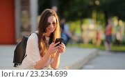 Купить «Девушка слушает музыку в городе», видеоролик № 23234699, снято 21 июня 2016 г. (c) Дмитрий Травников / Фотобанк Лори
