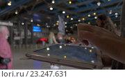 Купить «Woman typing on tablet PC in shopping centre hall», видеоролик № 23247631, снято 22 апреля 2016 г. (c) Данил Руденко / Фотобанк Лори