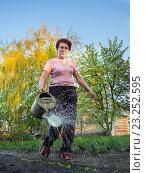 Купить «Счастливая дачница поливает грядки из лейки», эксклюзивное фото № 23252595, снято 4 мая 2016 г. (c) Вячеслав Палес / Фотобанк Лори