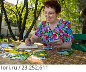 Купить «Пожилая женщина записывает в тетрадь данные по высаженным семенам», эксклюзивное фото № 23252611, снято 5 мая 2016 г. (c) Вячеслав Палес / Фотобанк Лори