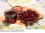 Купить «Ягоды спелой вишни и варенье в банке», эксклюзивное фото № 23257671, снято 13 июля 2016 г. (c) Яна Королёва / Фотобанк Лори