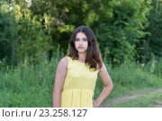 Купить «Teen girl in yellow dress standing in the park», фото № 23258127, снято 2 июля 2016 г. (c) Володина Ольга / Фотобанк Лори