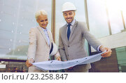 Купить «smiling businessmen with blueprint and helmets», фото № 23258847, снято 19 августа 2014 г. (c) Syda Productions / Фотобанк Лори