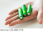Купить «close up of hand holding green alkaline batteries», фото № 23260119, снято 3 июня 2016 г. (c) Syda Productions / Фотобанк Лори