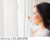 Купить «close up of woman looking through window», фото № 23260699, снято 23 марта 2016 г. (c) Syda Productions / Фотобанк Лори