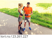 Купить «happy couple with roller skates riding outdoors», фото № 23261227, снято 5 июля 2015 г. (c) Syda Productions / Фотобанк Лори