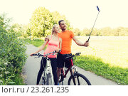Купить «couple with bicycle and smartphone selfie stick», фото № 23261235, снято 5 июля 2015 г. (c) Syda Productions / Фотобанк Лори