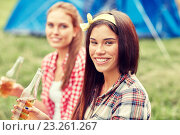 Купить «happy young women with tent and drinks at campsite», фото № 23261267, снято 25 июля 2015 г. (c) Syda Productions / Фотобанк Лори