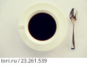 Купить «cup of black coffee with spoon and saucer on table», фото № 23261539, снято 21 февраля 2015 г. (c) Syda Productions / Фотобанк Лори