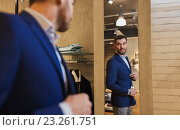 Купить «man trying jacket on at mirror in clothing store», фото № 23261751, снято 1 апреля 2016 г. (c) Syda Productions / Фотобанк Лори