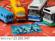 """Карта """"Тройка"""" и модели городского транспорта на фоне из проездных билетов (2016 год). Редакционное фото, фотограф Денис Ларкин / Фотобанк Лори"""