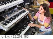 Купить «Girl choosing synthesizer in store», фото № 23268183, снято 13 июля 2020 г. (c) Яков Филимонов / Фотобанк Лори