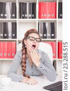 Купить «Женщина зевает на рабочем месте», фото № 23288515, снято 29 июня 2016 г. (c) Darkbird77 / Фотобанк Лори