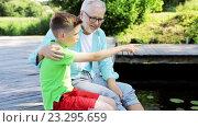 Купить «grandfather and grandson sitting on river berth 29», видеоролик № 23295659, снято 16 июля 2016 г. (c) Syda Productions / Фотобанк Лори