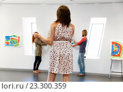 Купить «Young artists in gallery hanging painting on walls», фото № 23300359, снято 24 января 2015 г. (c) Sergey Nivens / Фотобанк Лори