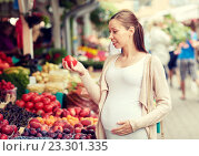 Купить «pregnant woman choosing food at street market», фото № 23301335, снято 27 июля 2015 г. (c) Syda Productions / Фотобанк Лори
