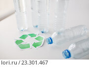 Купить «close up of plastic bottles and recycling symbol», фото № 23301467, снято 3 июня 2016 г. (c) Syda Productions / Фотобанк Лори