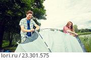 Купить «happy couple setting up tent outdoors», фото № 23301575, снято 25 июля 2015 г. (c) Syda Productions / Фотобанк Лори