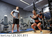 Купить «man and woman with barl flexing muscles in gym», фото № 23301811, снято 19 апреля 2015 г. (c) Syda Productions / Фотобанк Лори