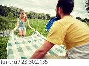 Купить «happy couple laying picnic blanket at campsite», фото № 23302135, снято 25 июля 2015 г. (c) Syda Productions / Фотобанк Лори