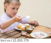 Купить «Девочка сосредоточено накладывает кондитерскую глазурь на пасхальные кексы», фото № 23303179, снято 3 апреля 2016 г. (c) Иванов Алексей / Фотобанк Лори