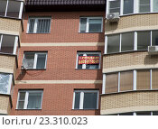 Объявление о продаже дома в окне кирпичного многоквартирного дома (2016 год). Редакционное фото, фотограф Малахов Алексей / Фотобанк Лори