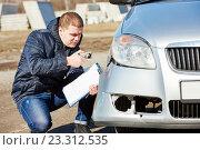 Купить «Insurance agent recording car damage on claim form», фото № 23312535, снято 15 марта 2016 г. (c) Дмитрий Калиновский / Фотобанк Лори