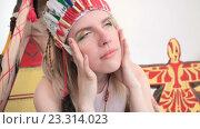 Молодая блондинка в костюме американских индейцев трогает лицо. Стоковое видео, видеограф Алексндр Сидоренко / Фотобанк Лори