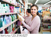 Купить «woman picking bottles with shampoo and conditioner from shelf in cosmetics store», фото № 23314027, снято 16 июля 2019 г. (c) Яков Филимонов / Фотобанк Лори